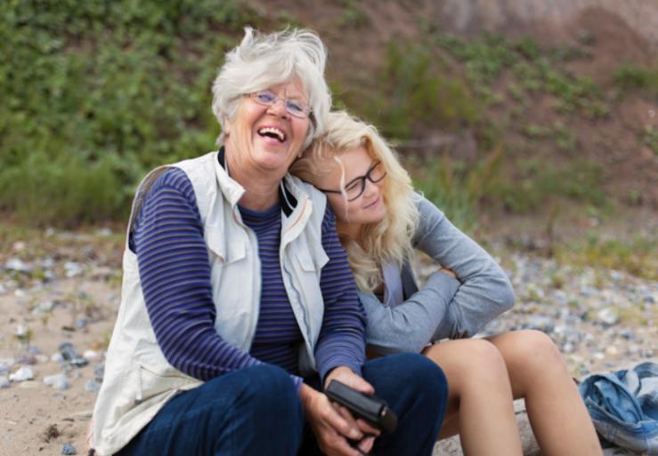 En äldre och en yngre kvinna sitter tillsammans på en strand