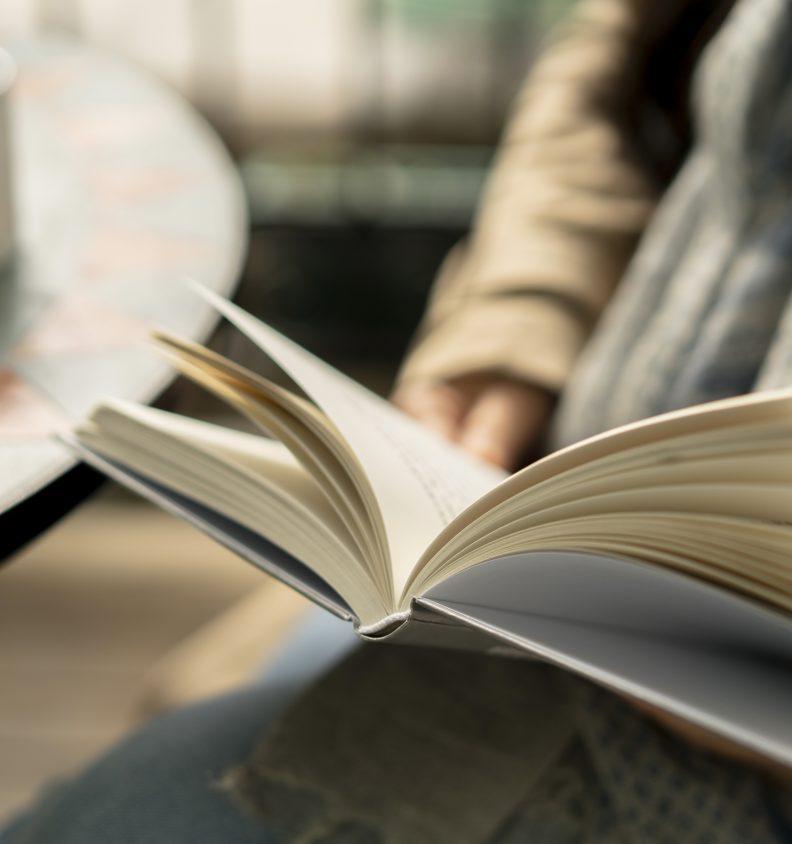 En person läser en inbunden bok
